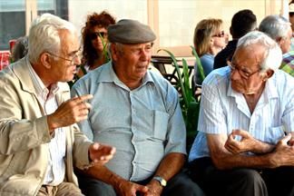 three older men sitting on a bench conversing