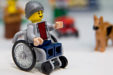 lego figure of a hat-wearing boy in a wheelchair