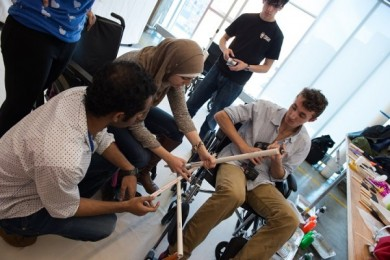 A group of engineering students work on a wheelchair-based painting mechanism during the Fit-IN conference
