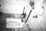 black and white photo of a latrine in india on ground floor