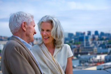 mature couple looking at each other with cityscape in the background