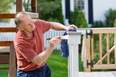 Mature man painting fence outdoors