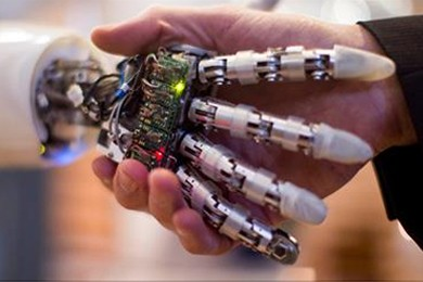 close up of robot hand and human hand shaking hands