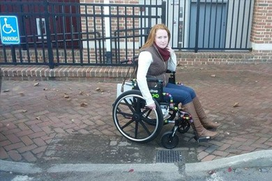 woman in wheelchair on curb ramp