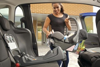 woman putting baby carrier into back seat of car