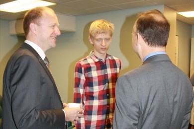 two ceos speak with a young autistic man