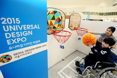 """A boy tries to shoot a basket designed to be wheelchair-friendly at the """"2015 Universal Design Expo"""" which opened at the Dongdagemun Design Plaza"""