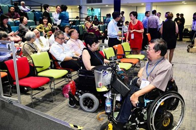 people in an auditorium designed for disabilities including a wheelchair user