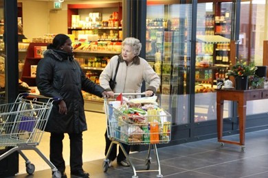 adult and older adult shoppers at the entrance of supermarket