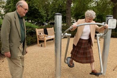 elderly couple using playground exercise equipment - woman is using elliptical machine