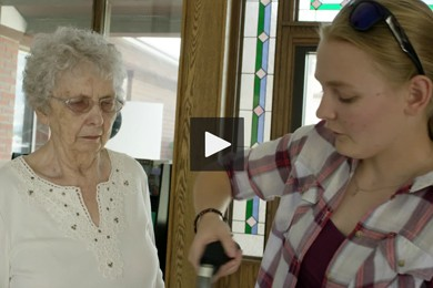 screenshot of video. mary hood and elderly woman. mary hood is holding smart cane