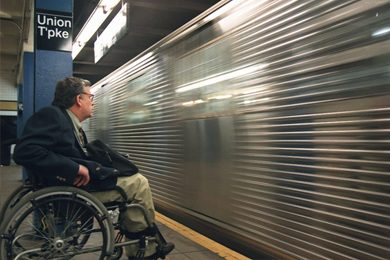 man in wheelchair next to moving subway train in nyc