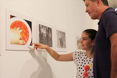 Darren and Jazzie McCallum look at her final photographs at Spectrum. (105.7 ABC Darwin: Emilia Terzon)