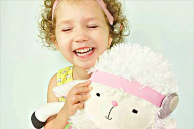 Elyse Wright, 3, holding her lamb Weesie Pal. Like her, it sports a bone-anchored hearing aid commonly used for microtia. (Courtesy Erin Wozniak)