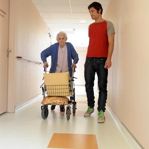 elderly woman walking using a walker with younger man walking along side her